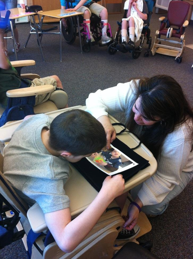 A boy and an adult during a lesson using a picture. The boy has his face very close to the picture.