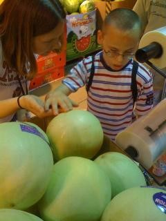 Boy at grocery store. An adult is helping him explore what melons feel like. She has her hand under his.