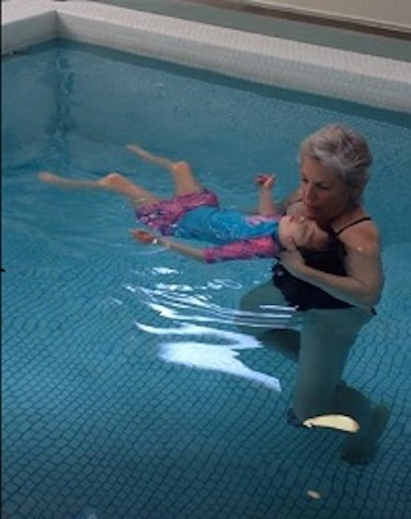 Camilla swims in the pool with her grandma.