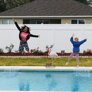 Two young girls, on of whom is deaf-blind, jumping into a pool.