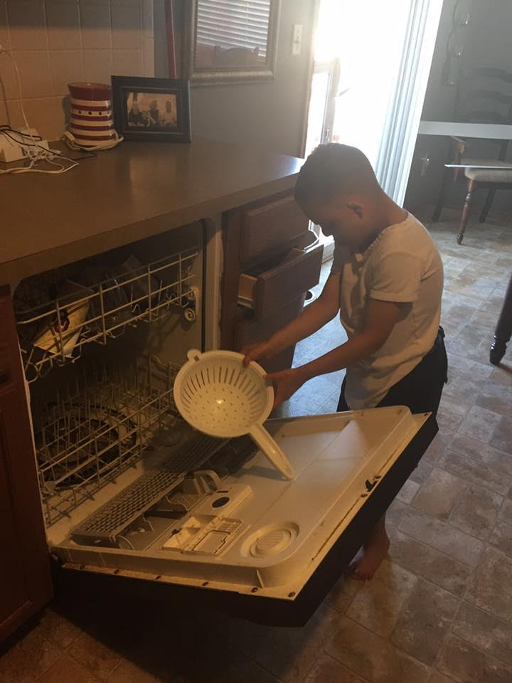A young man who is deaf-blind is taking a dish out of a dishwasher.