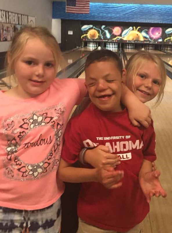 A boy who is deaf-blind is at a bowling alley with two girls. They have their arms around each other and are smiling.