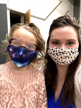 An adult woman who is a teacher, and a girl who is a student with deaf-blindness, standing side by side looking at the camera. Both are wearing masks over their mouths because of the COVID-19 pandemic.