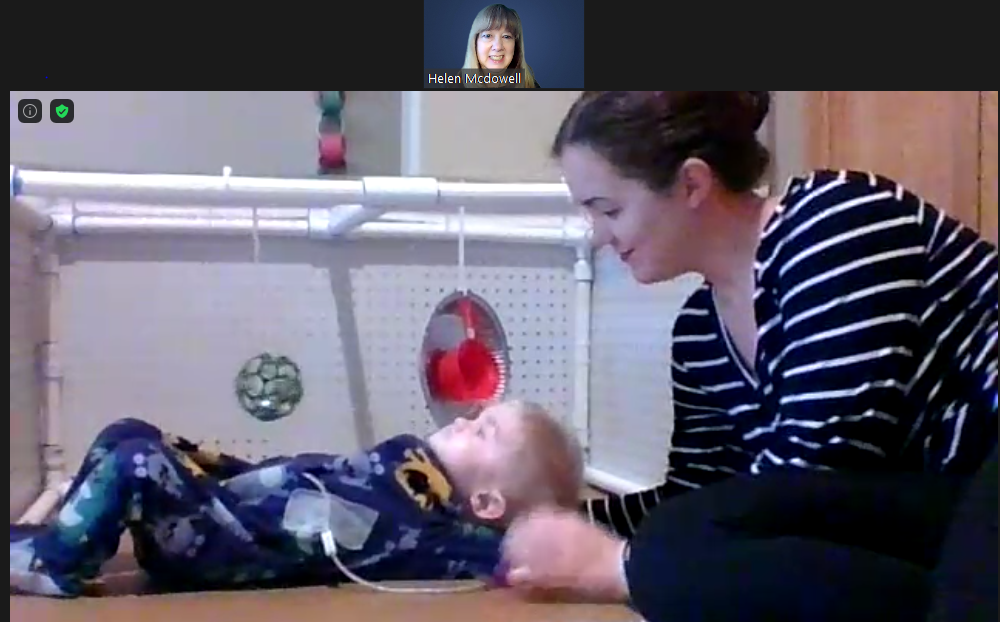 Screenshot of zoom call of teacher and child with parent. 9-month-old child lying on back with toys near by. His mom his learning over him, smiling gently.