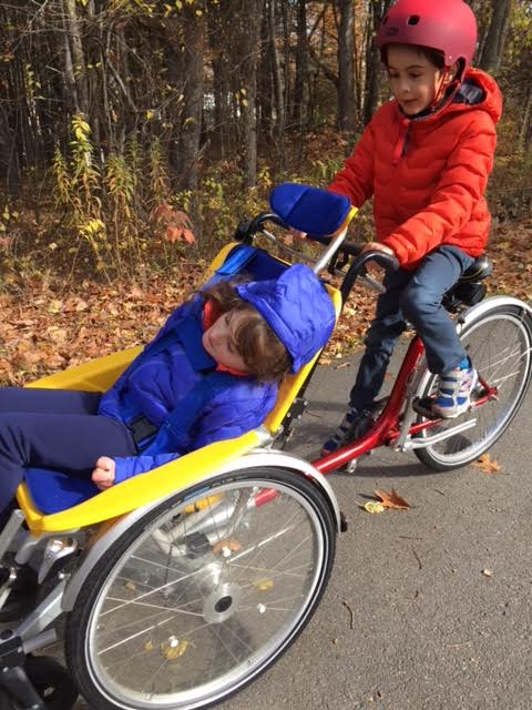 Jack and grace riding an accessible bike.