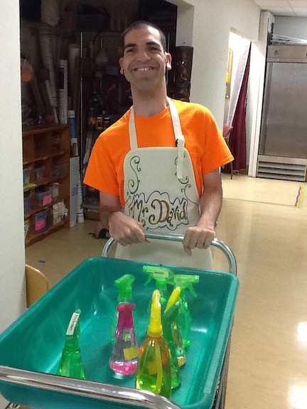 David pushing cart with cleaning supplies.