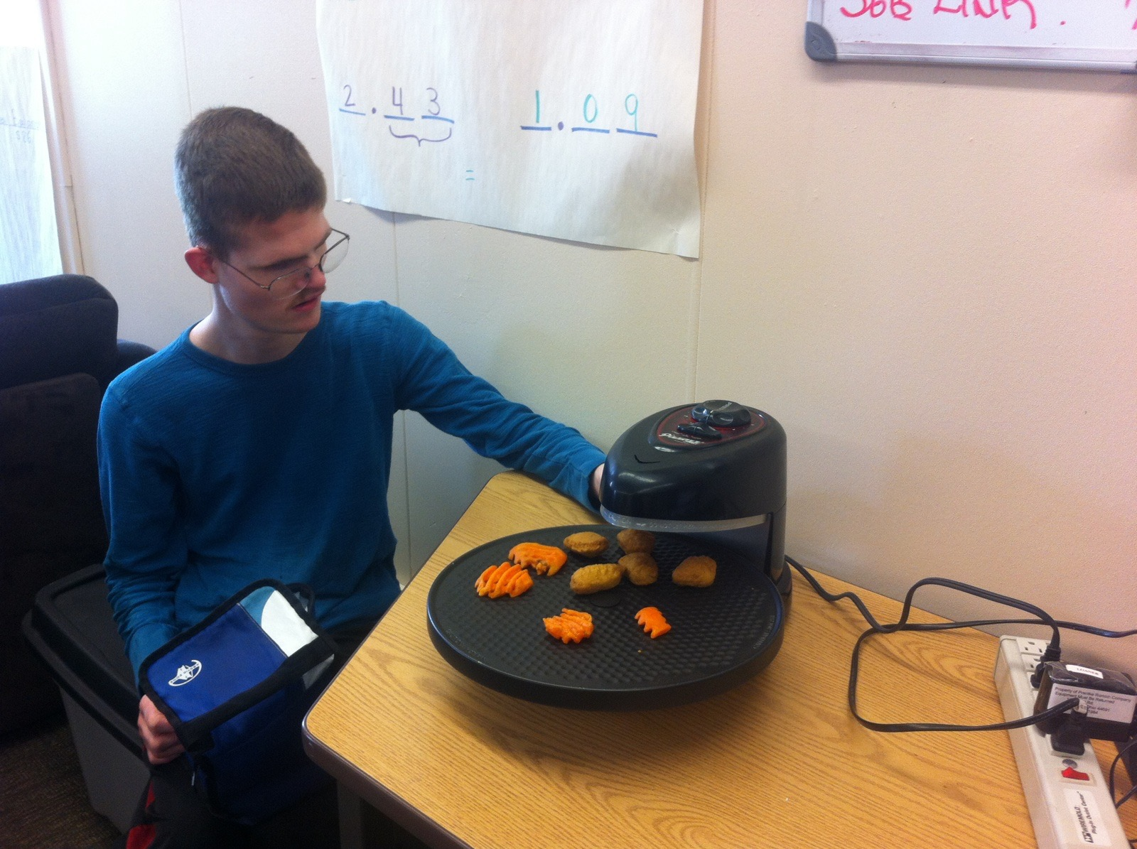 A young man who is deaf-blind is sitting at a table cooking carrots and potatoes on an electronic cooking device.