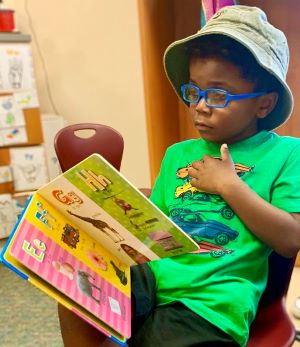 A young boy in a classroom reading a children's book. He is wearing glasses and a hat.