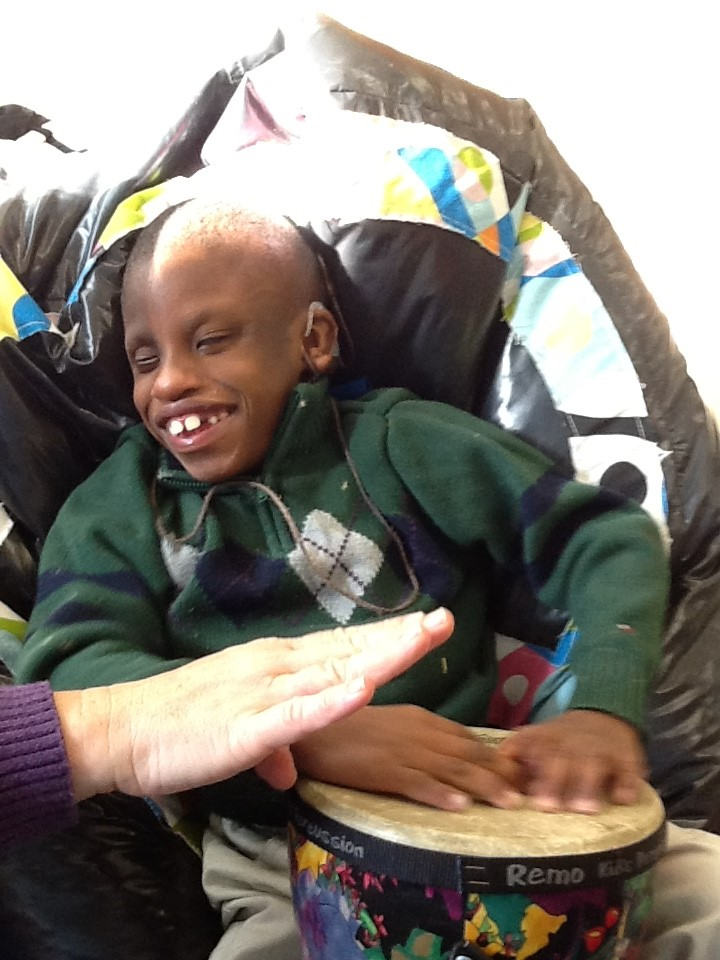Young boy sitting in a wheelchair, holding a tambourine on his lap and touching it with both hands. Big smile on his face.