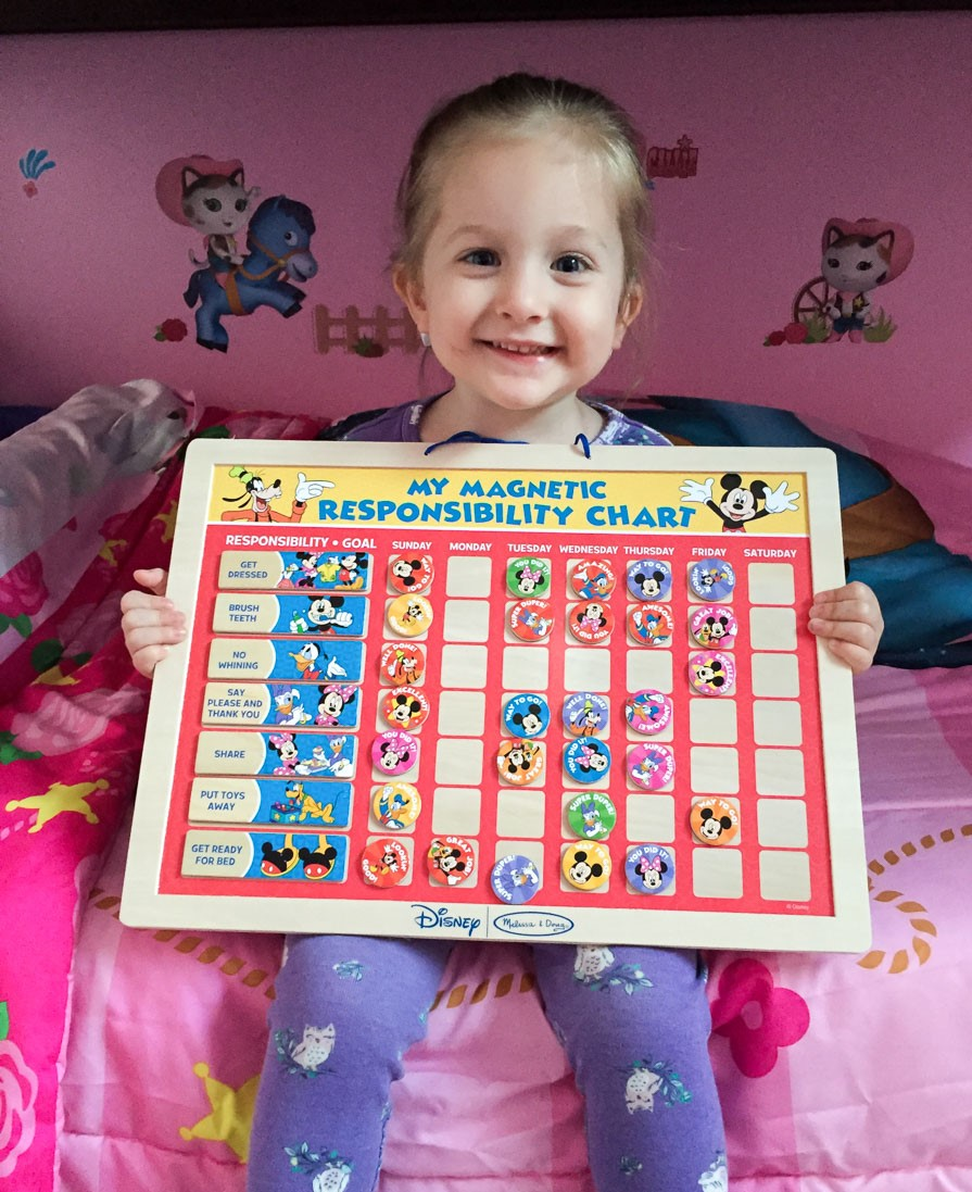"A young girl holding a chart containing Disney character magnets. It reads ""My Magnetic Responsibility Chart."