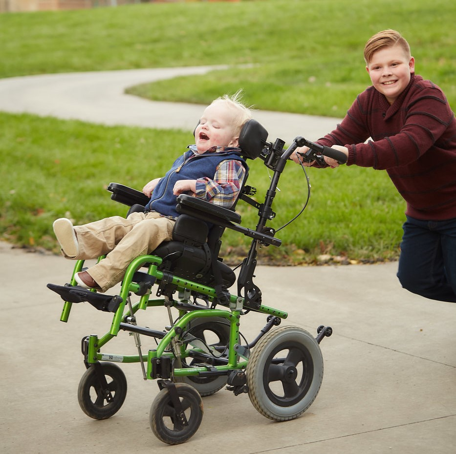 A 4-year old boy with deaf-blindness who is in a wheelchair is being pushed by his 9-year-old brother. It looks like they are going fast and both have big smiles.