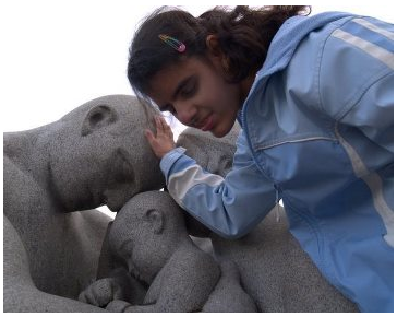 A teenage girl who is deaf-blind has her hand on a statue of an adult holding a baby.