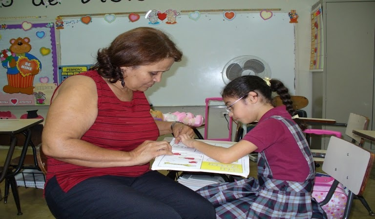 Young girl working with teacher.