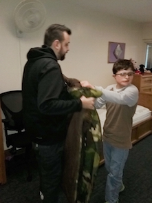 Omar helps Nathanial put on his jacket.
