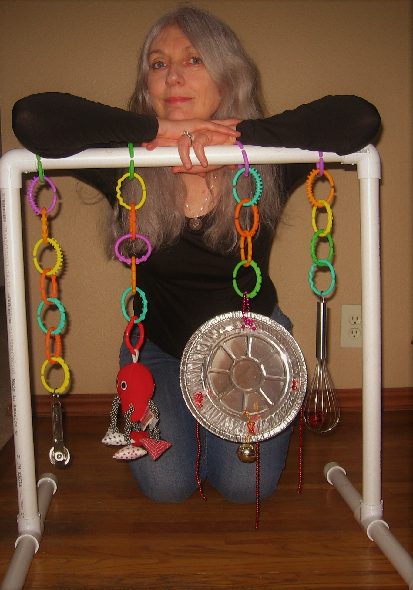 A woman is kneeling on a wood floor behind a homemade pvc pipe frame. She is leaning forward with her arms resting on the top of the frame. Hanging from it are four colored plastic chains. At the end of each chain is an object—a measuring spoon, a stuffed