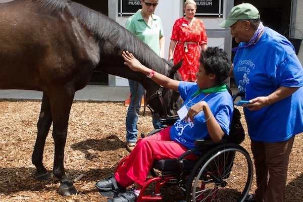 Young woman in wheelchair petting horse.
