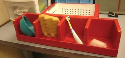 A large red container with four sections, each containing a different object: a bowl, a sponge, a toothbrush, a bar of soap.