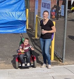 AN intervener stands next to a child in a motorized wheelchair.
