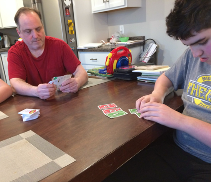 A family plays a braille uno card game.