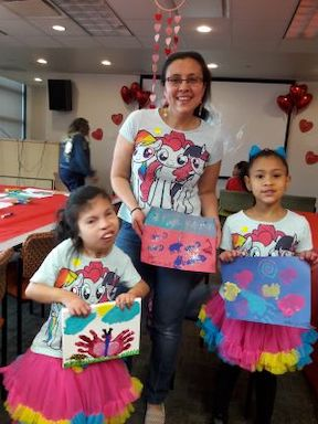 A mother and her two young daughters, one of whom is deaf-blind, stand facing the camera. They are all holding small paintings that they created. In the background is a table with art supplies.